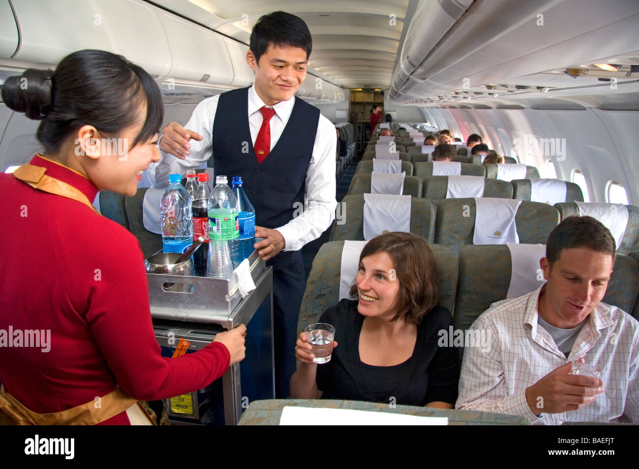 flight attendants serve beverages to passengers on a