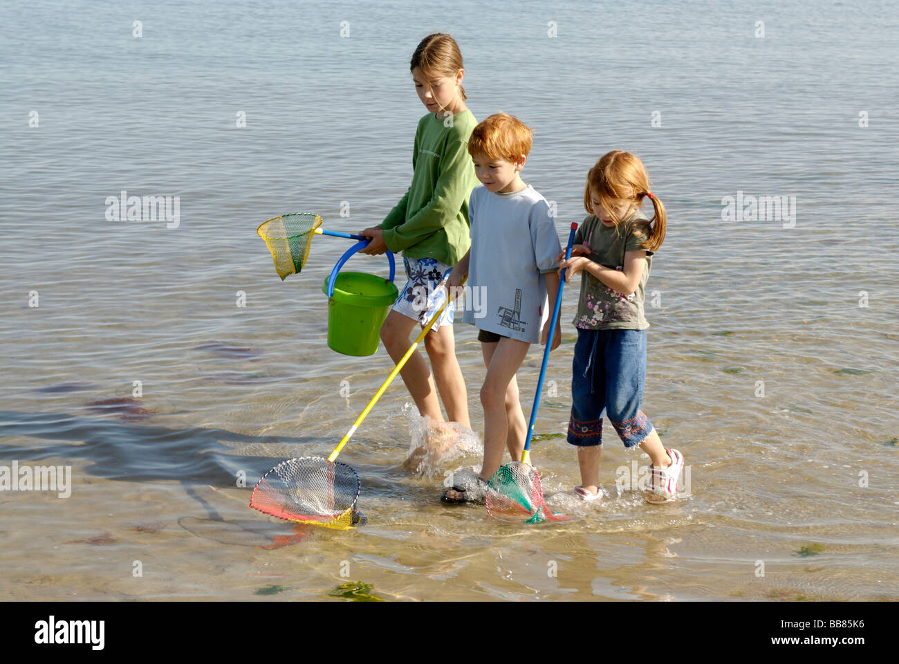 Children walking on the beach seaside with fishing net for Kids fishing net