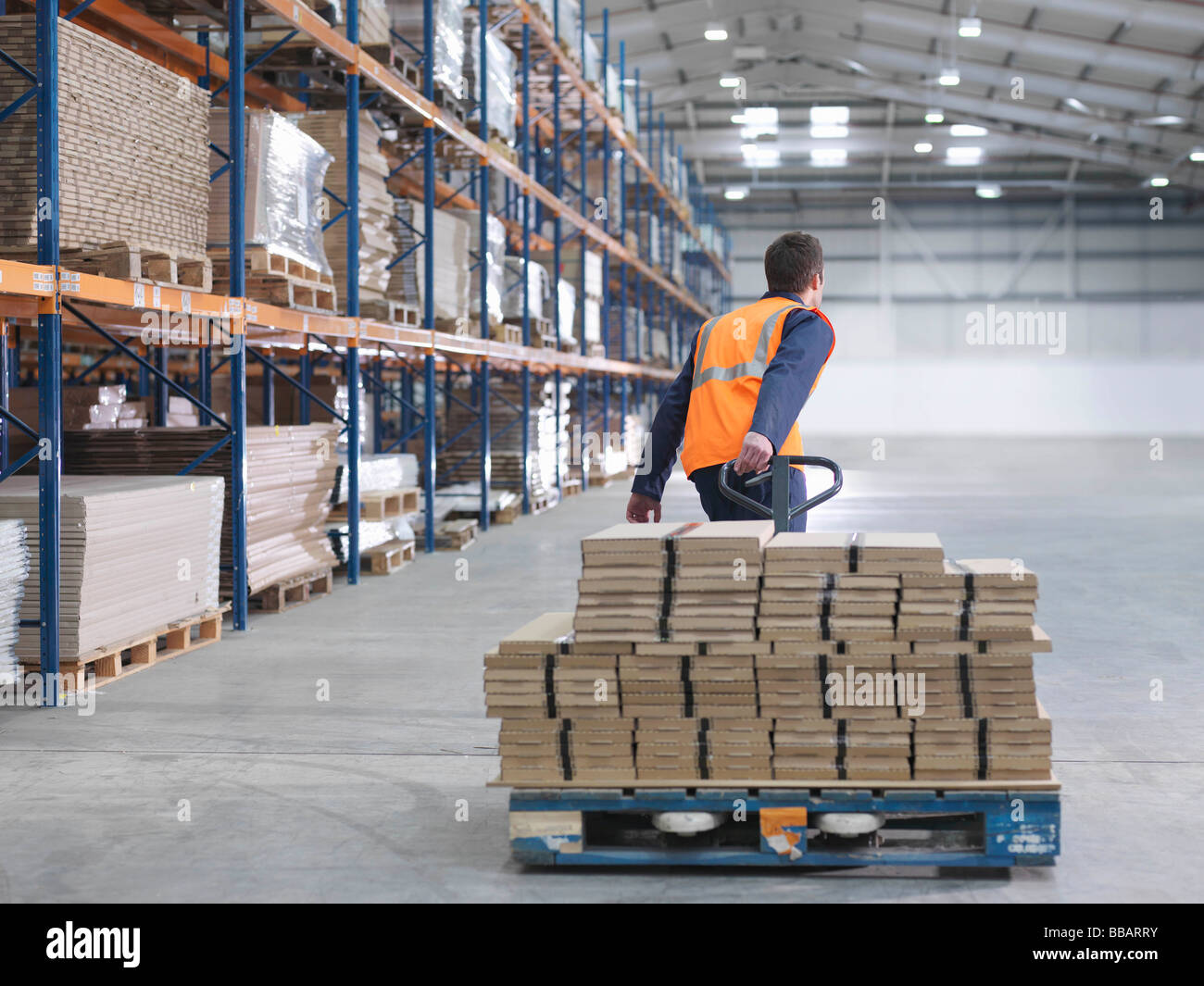 Worker Transporting Load In Warehouse Stock Foto