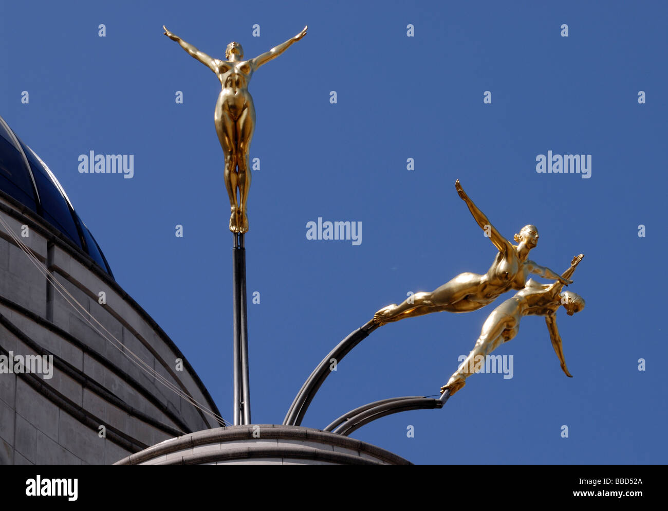 Gold leaf covered aluminium statues by Rudy Weller of the three graces diving from the roof of 1 Jermyn Street, Stock Photo
