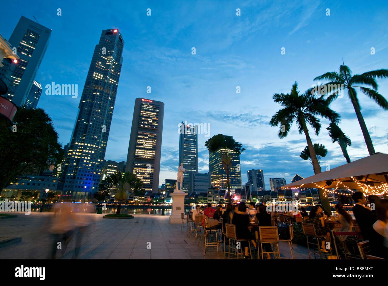 Skyline of Singapore  Raffles Statue street cafe South East Asia twilight Singapur Stock Photo