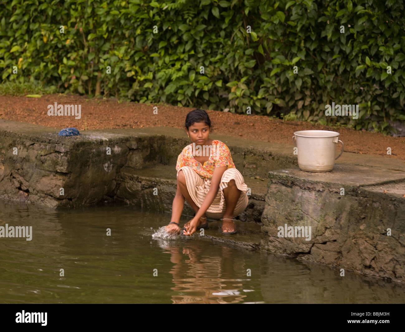 girl in india washing clothes in river water stock photo