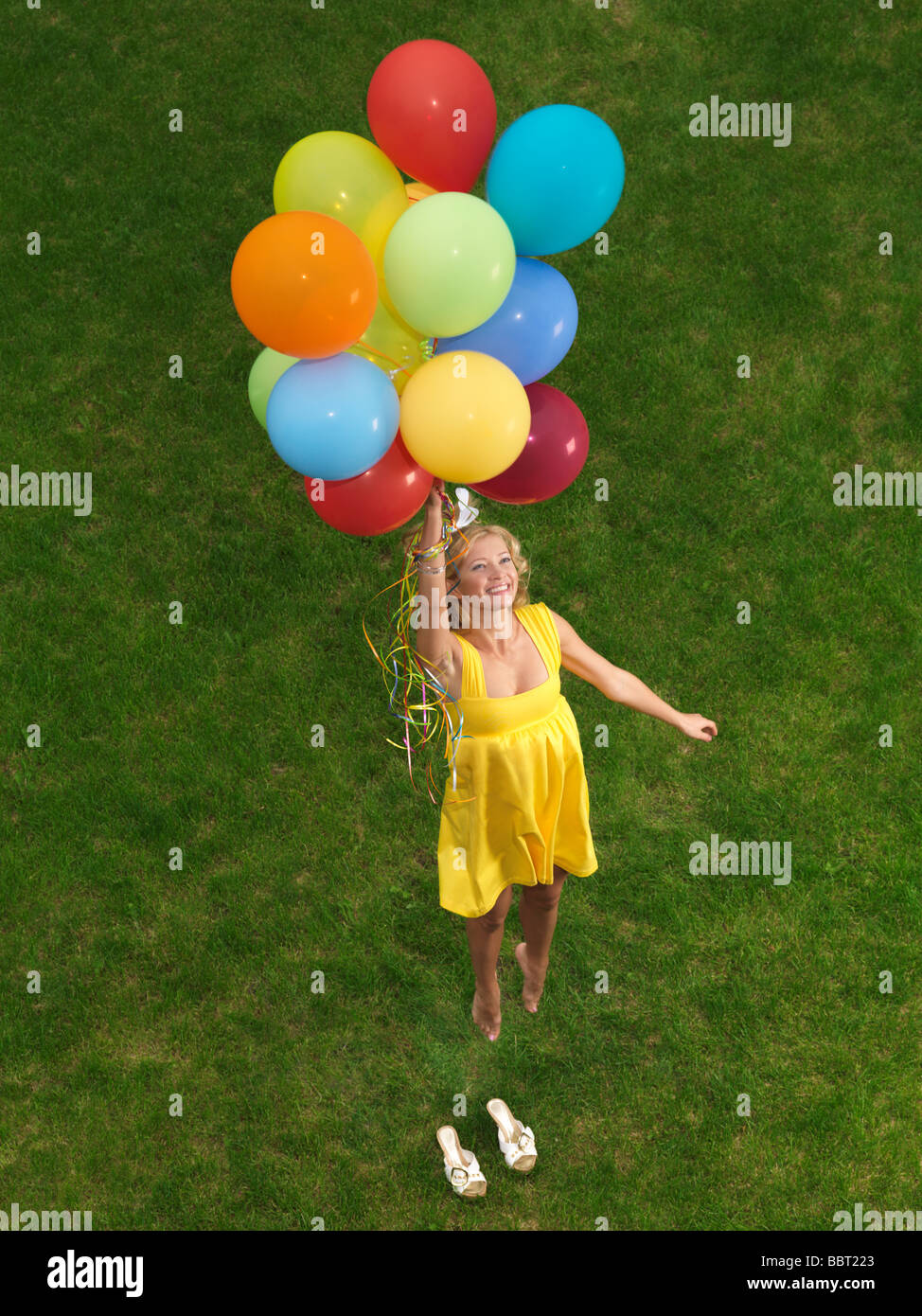 Young Happy Woman Flying Up From The Ground On Colorful ...