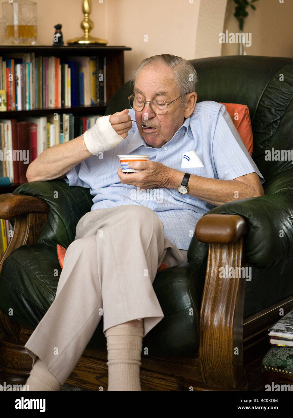 Old man sits in his favourite armchair eating a yoghurt for Sitting in armchair