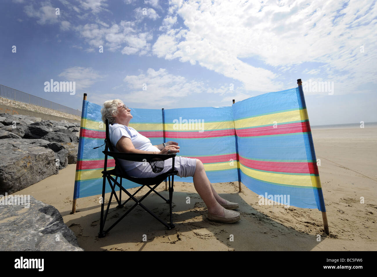 A  OLD AGE PENSIONER ENJOYS SUNBATHING ON A BRITISH BEACH WITH WINDBREAKER RE HOLIDAYS RETIREMENT OAPS PENSIONERS Stock Foto