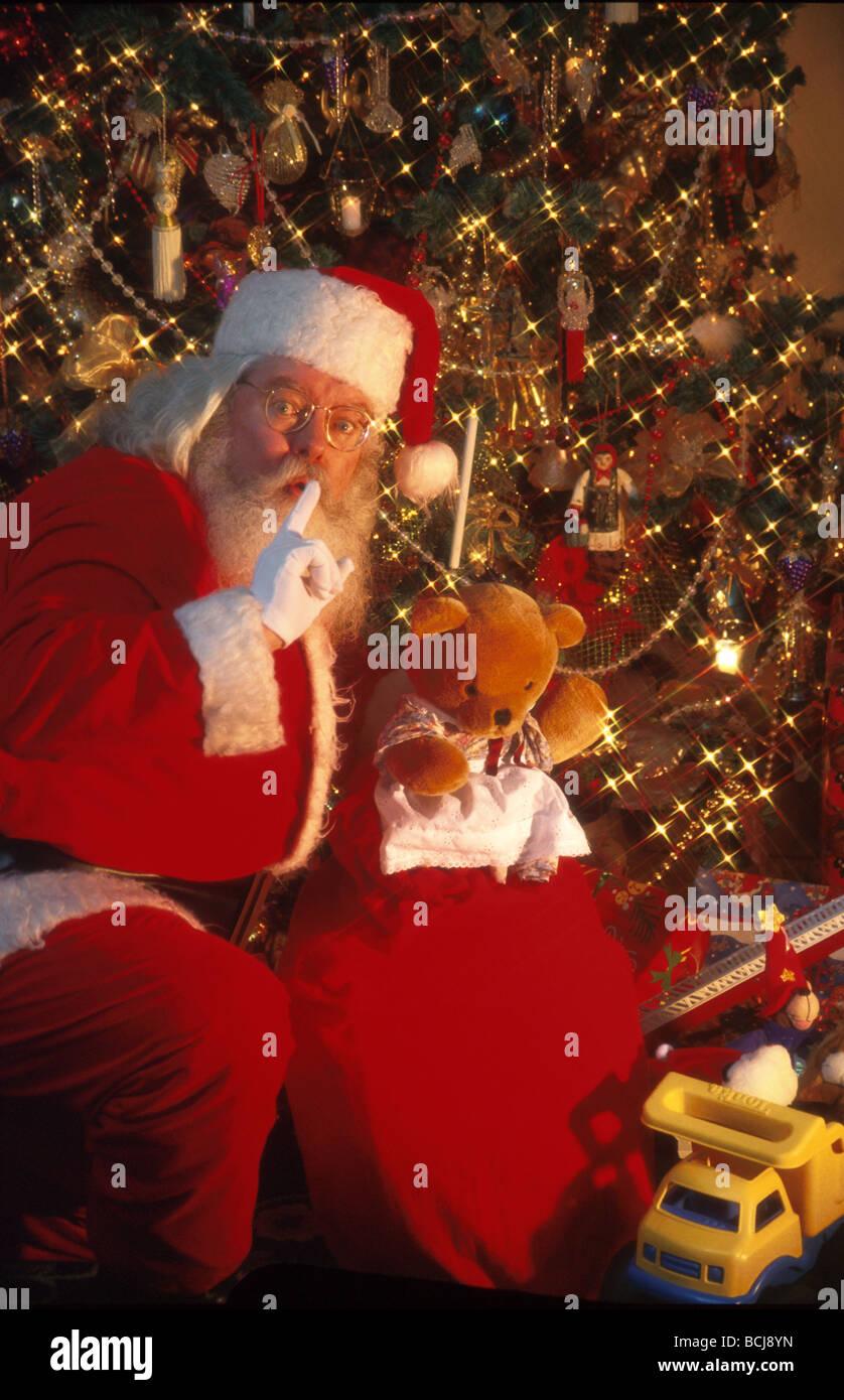 Toys Under Christmas Tree : Santa claus puts toys under christmas tree shhhh stock