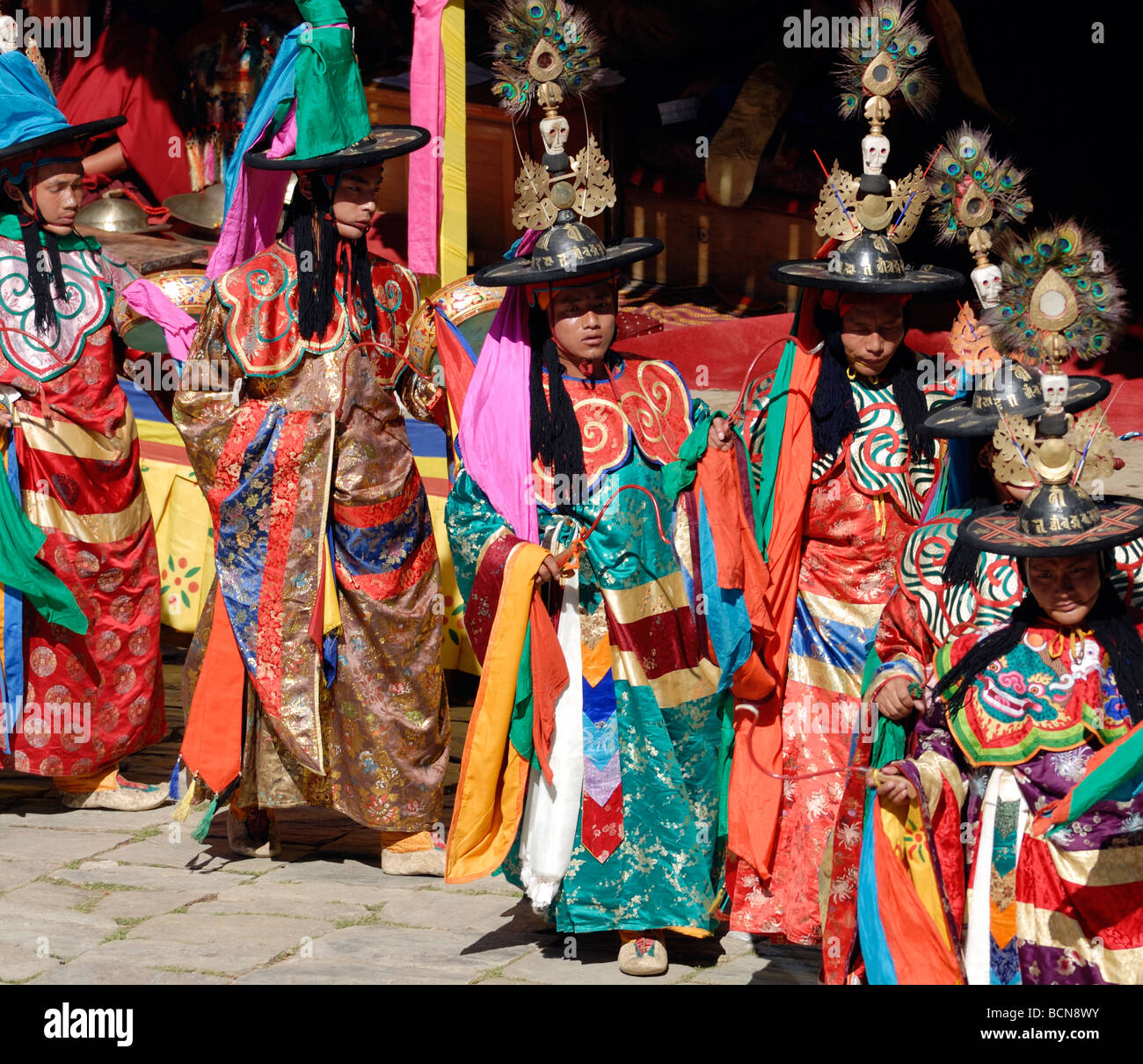 Black hat dancers dressed in gorgeous silk robes process across the courtyard of Mongar Dzong. Stock Photo