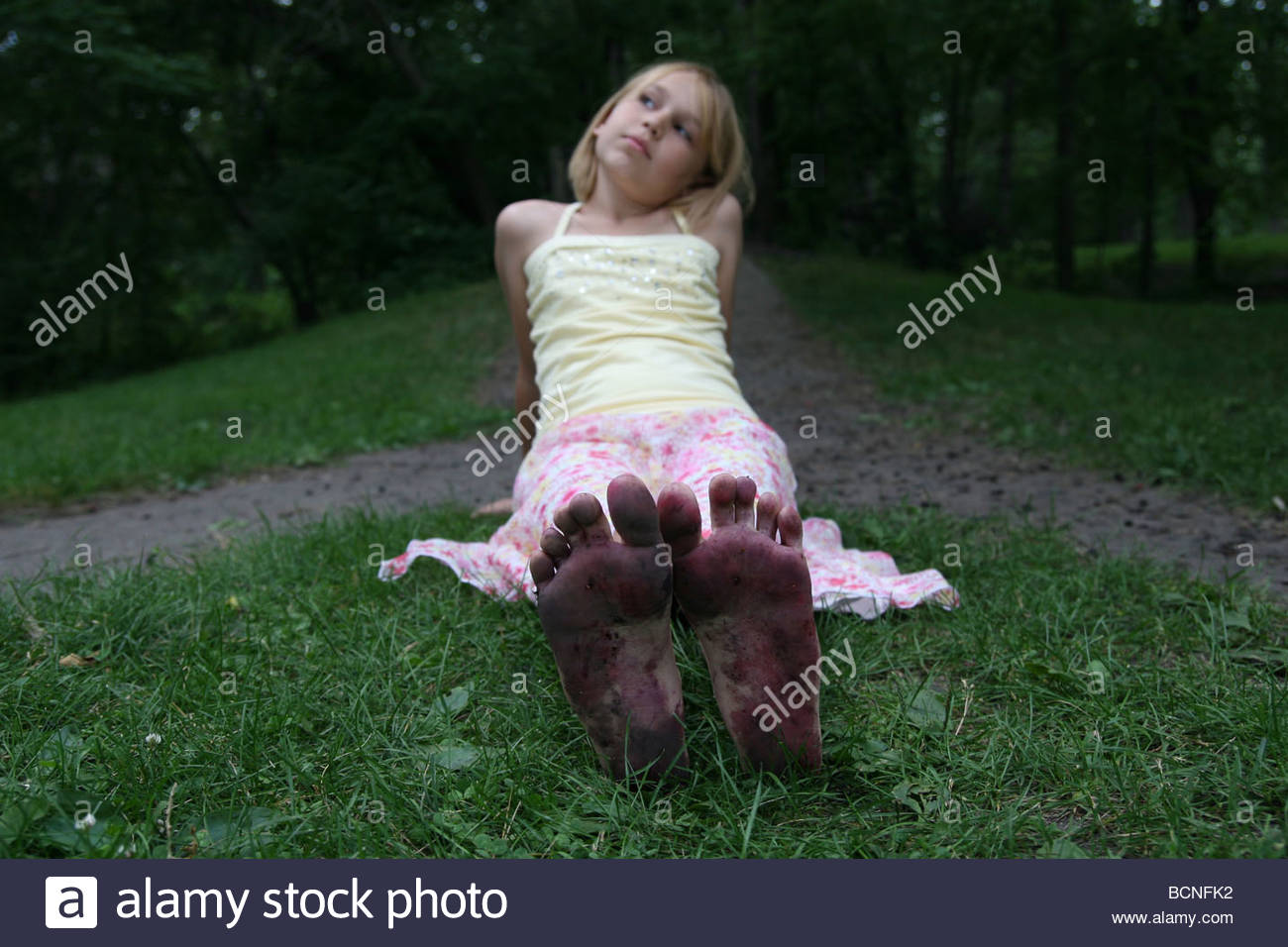 a-girl-sitting-in-the-grass-with-legs-st