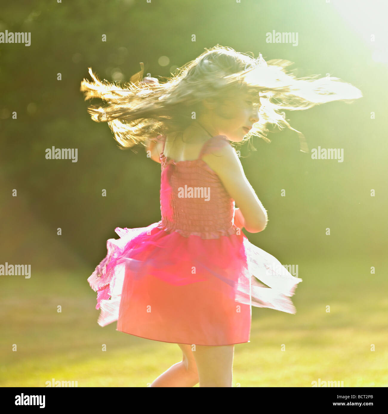 Young girl dancing in the summer sun. Stock Photo