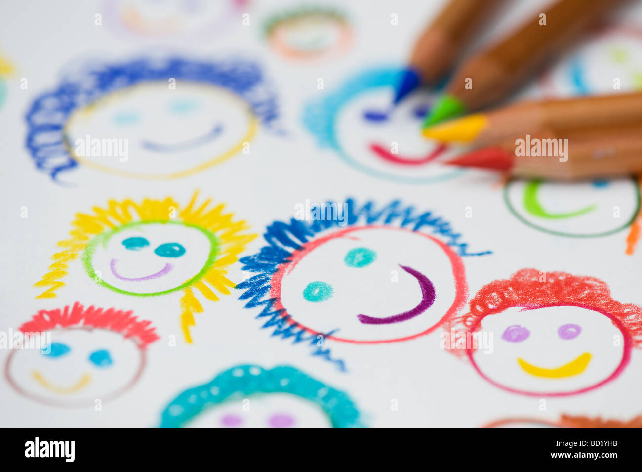 Childs coloured drawing of happy smiling faces with colouring pencils Stock Photo
