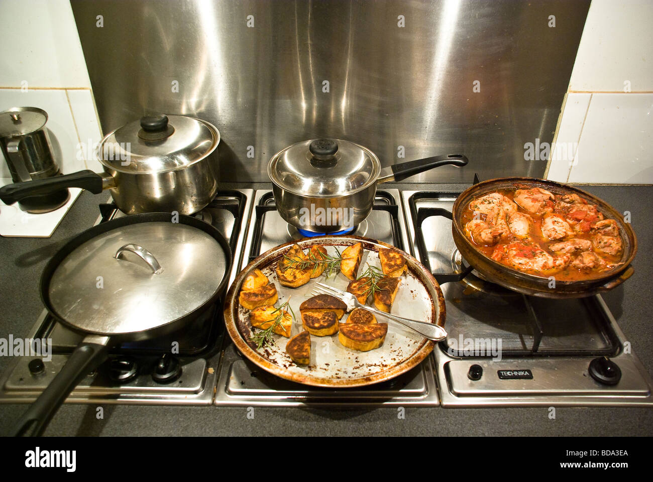 pots and pans on a gas stove top showing a chicken casserole dish and stock photo royalty free. Black Bedroom Furniture Sets. Home Design Ideas