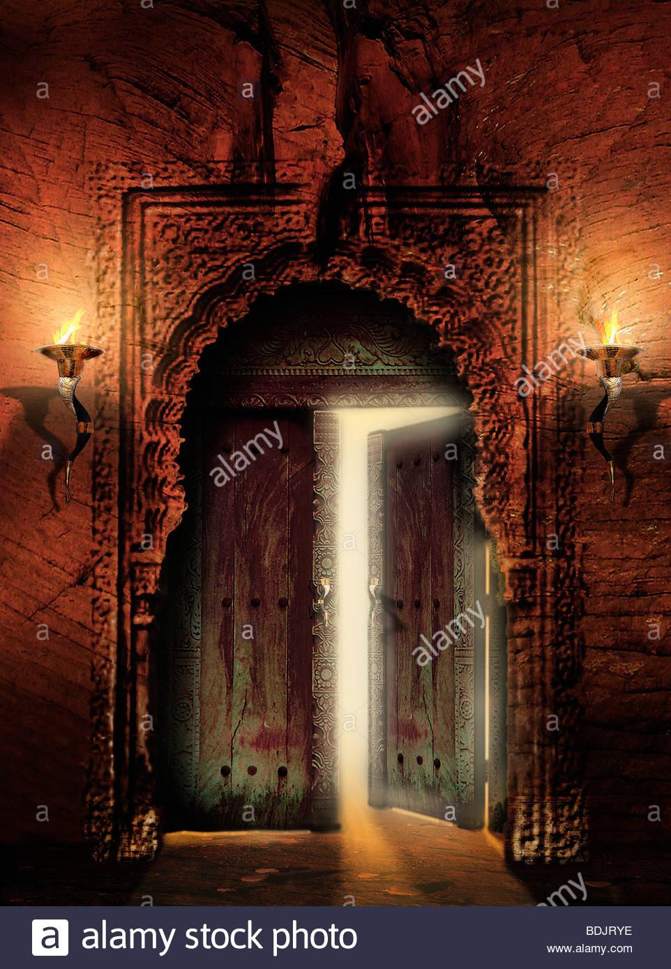 Ornate, ancient doorway with door partly open Stock Foto