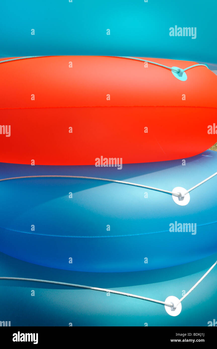 Abstract summer concept shot of colorful inflatable beach flotation rings Stock Photo