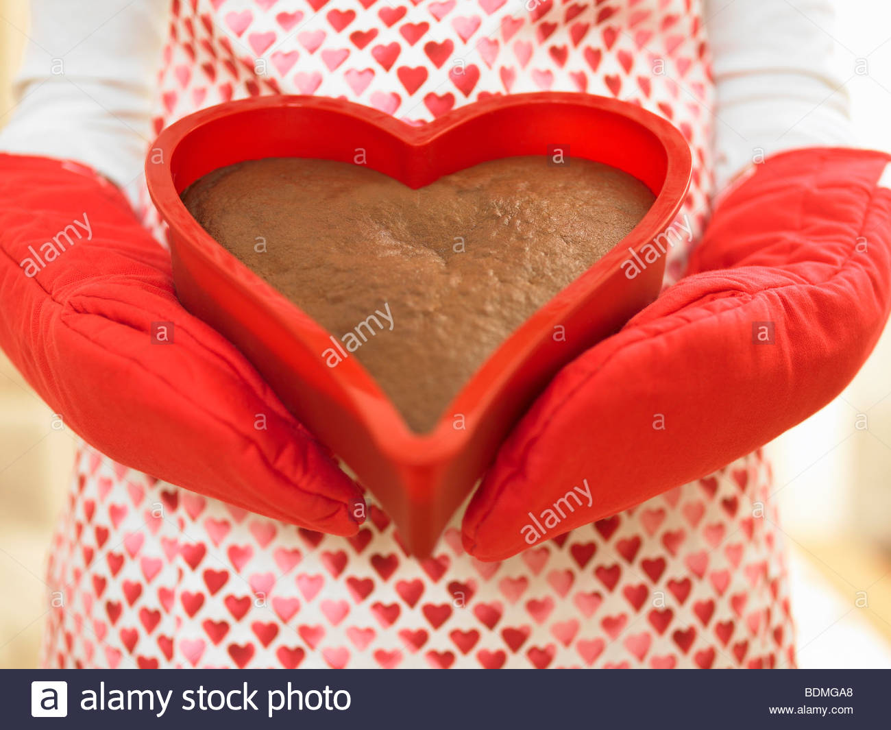 Close up of woman holding heart-shaped cake Stock Foto