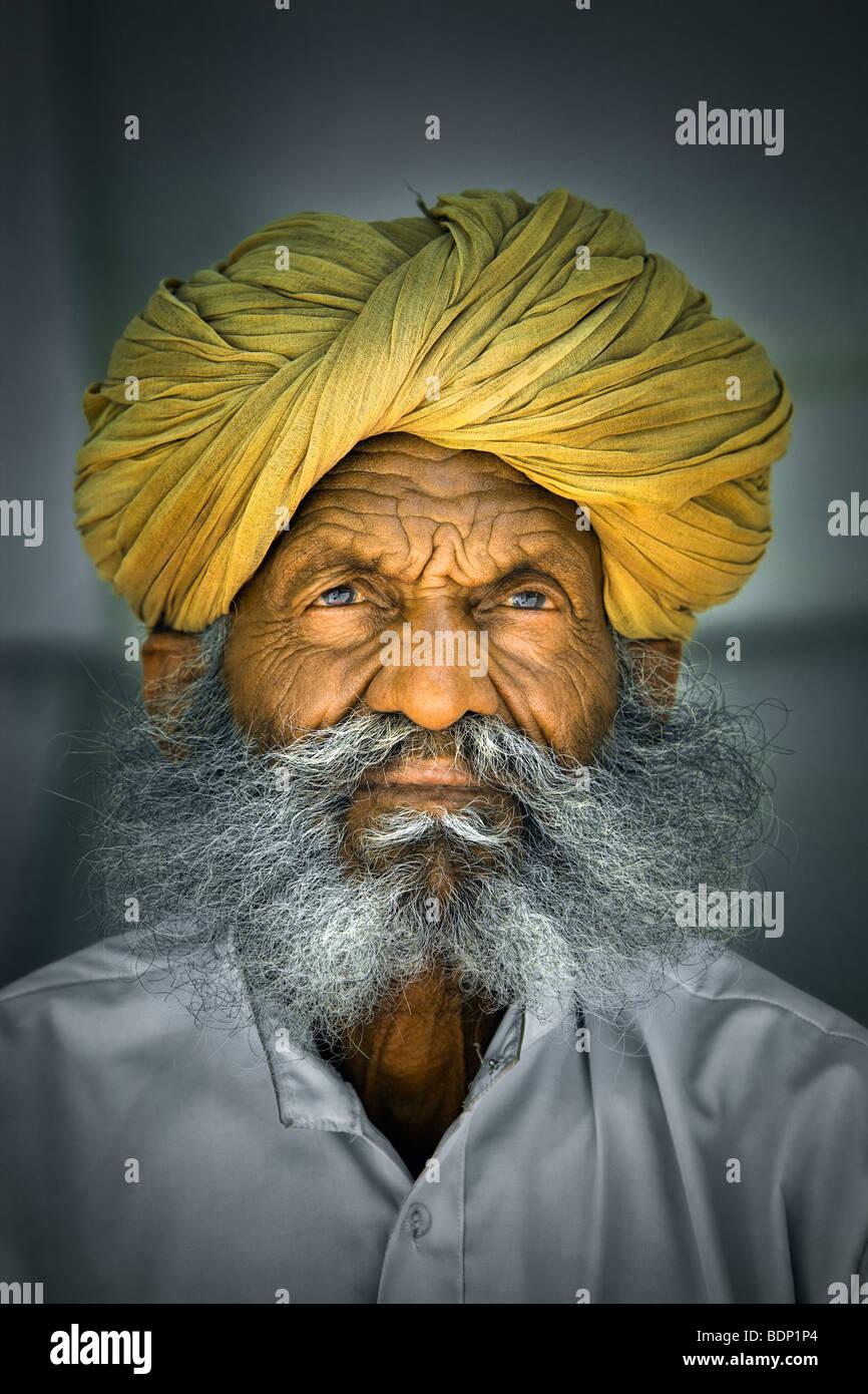 India, Rajasthan, Jodhpur, older Rajasthani Indian man with bushy gray beard wearing yellow turban Stock Foto