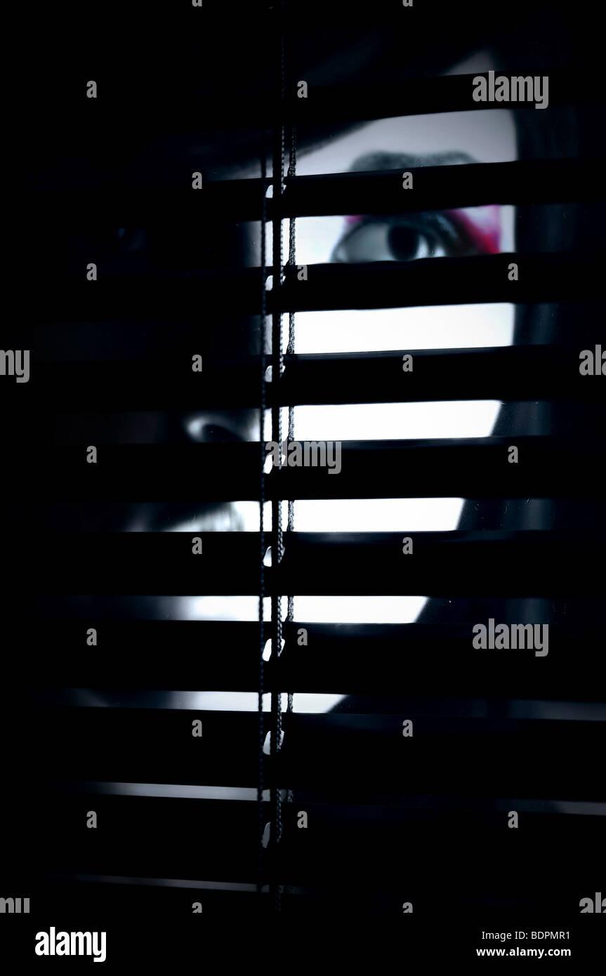 A partially hidden face of a young woman behind a screen Stock Foto
