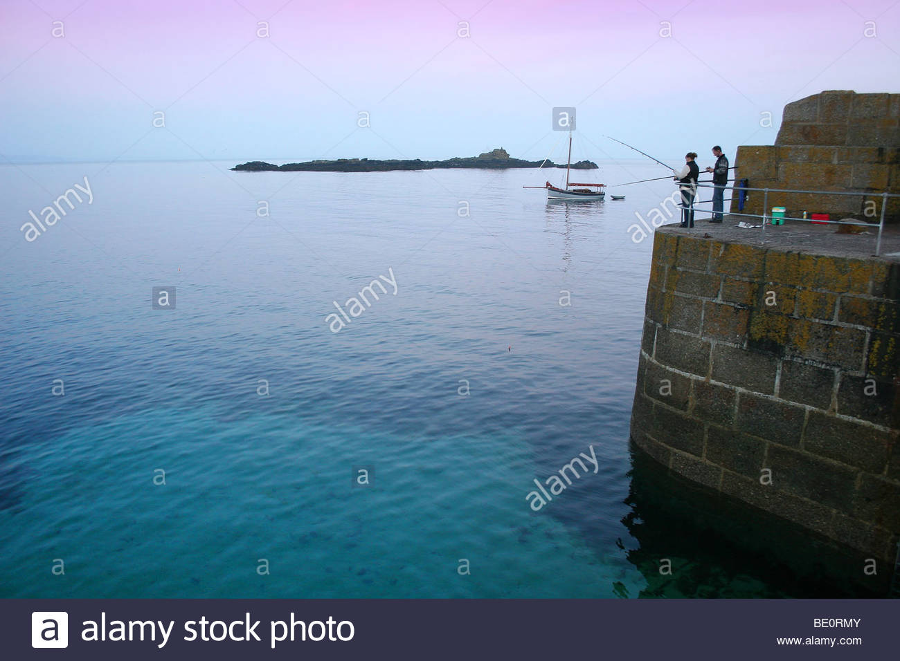 Two people fishing off the pier at the picturesque village for Fishing off a pier