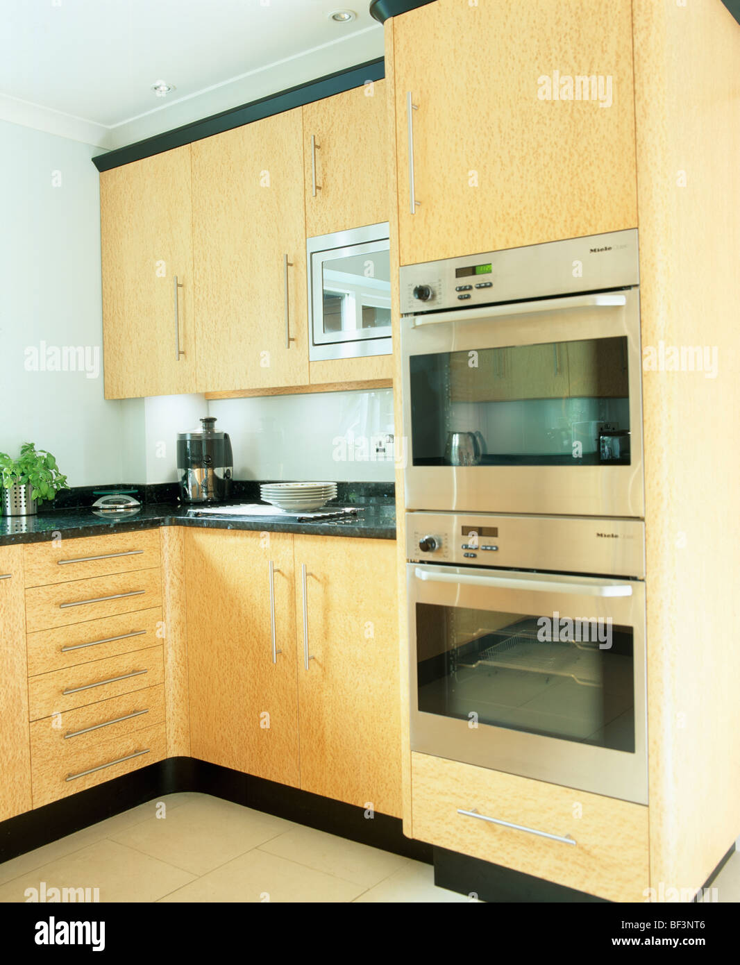 Eye level double oven in modern kitchen with pale wood for Eye level oven kitchen designs