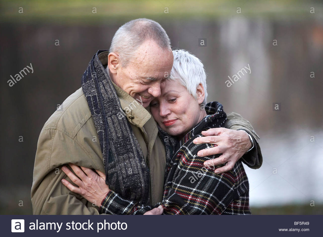 an ellderly couple is hugging each other dearly in a park