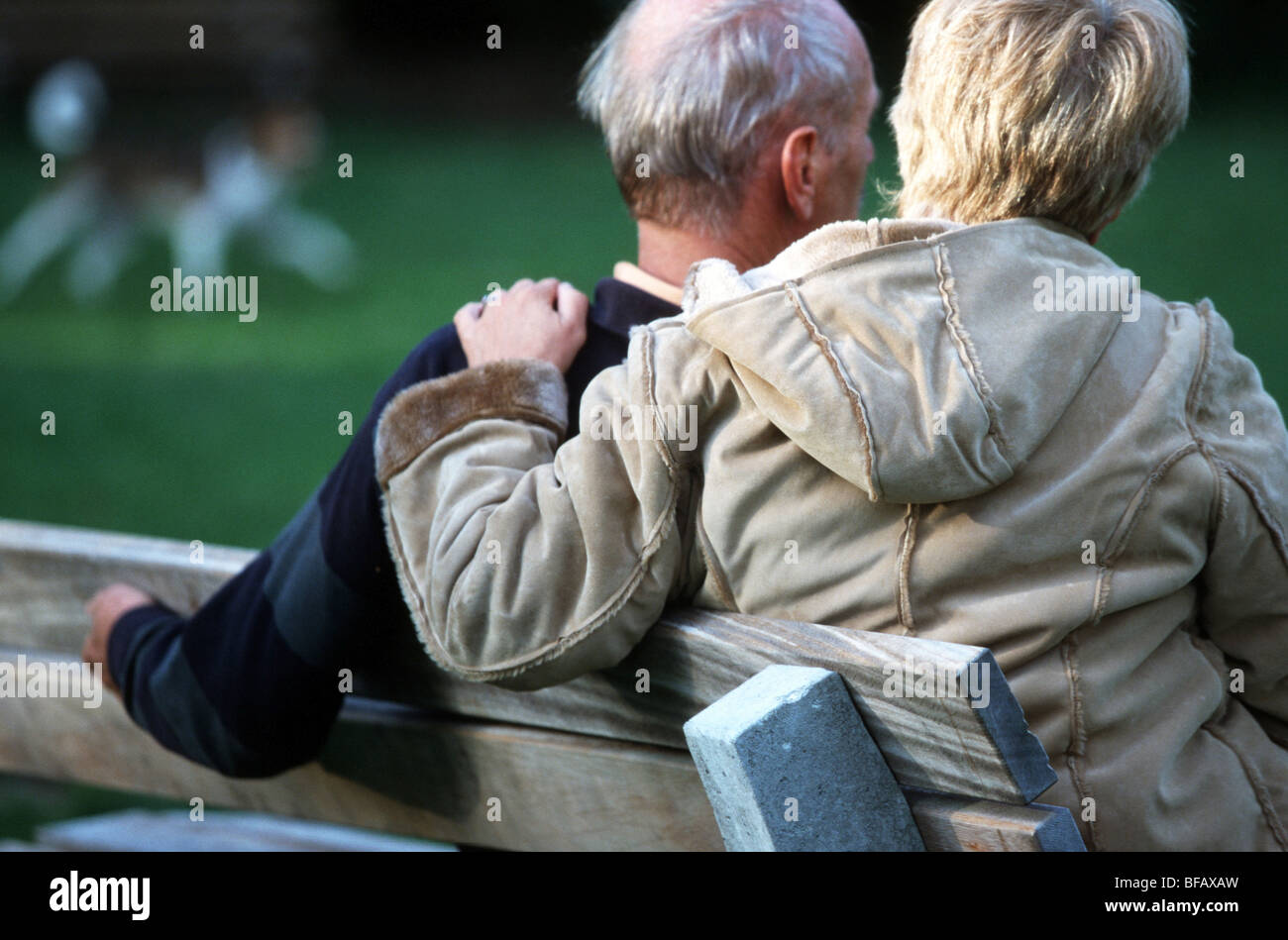 Worried pensioner couple sit on park bench, consolation, back view, woman hand on shoulder elderly man Stock Photo