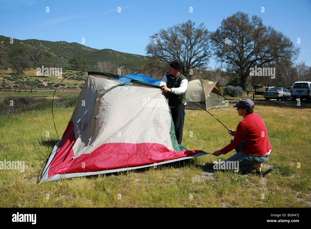 a man and woman camping and building a tent outdoors stock photo royalty free image 27553110. Black Bedroom Furniture Sets. Home Design Ideas