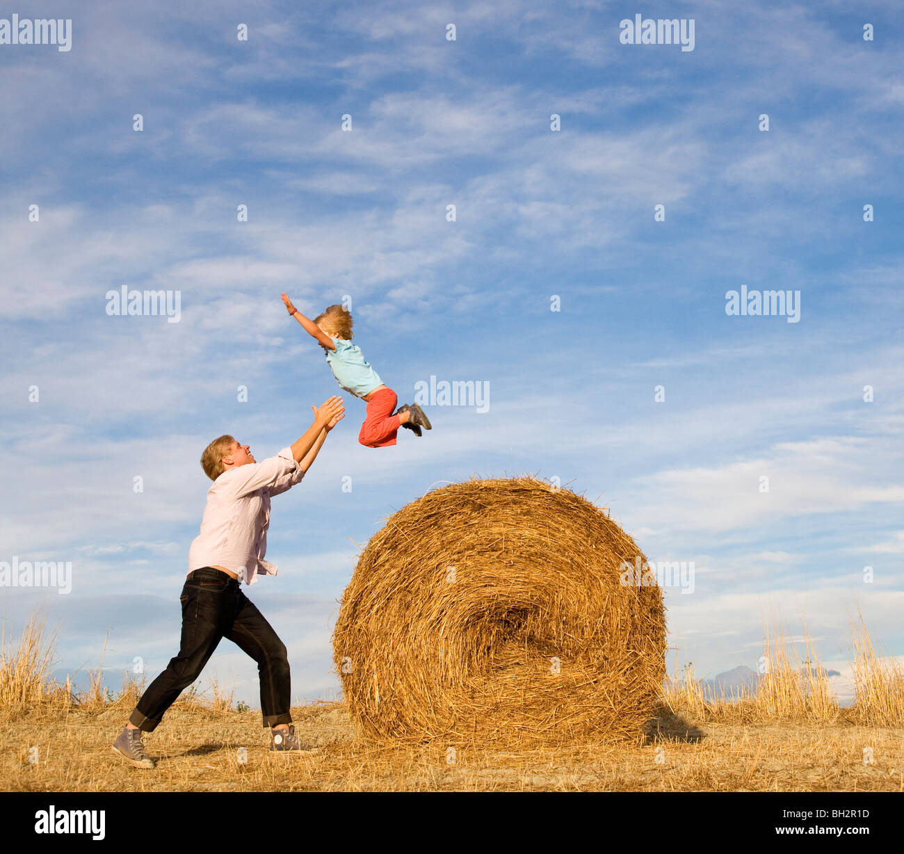 man catching boy jumping from hay bale Stock Foto