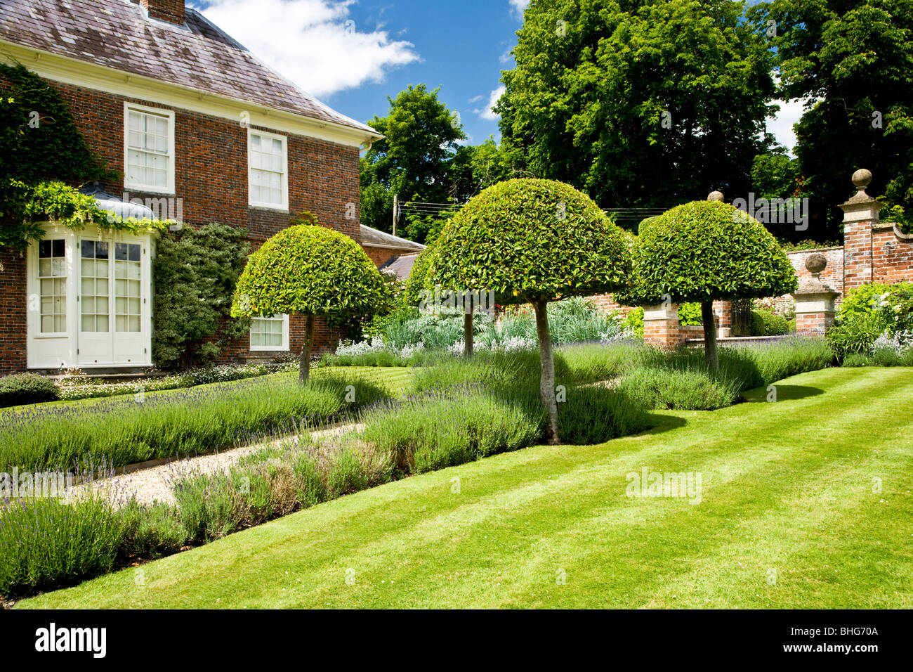Topiary and a lavender edged path in front of a grand for Country house online