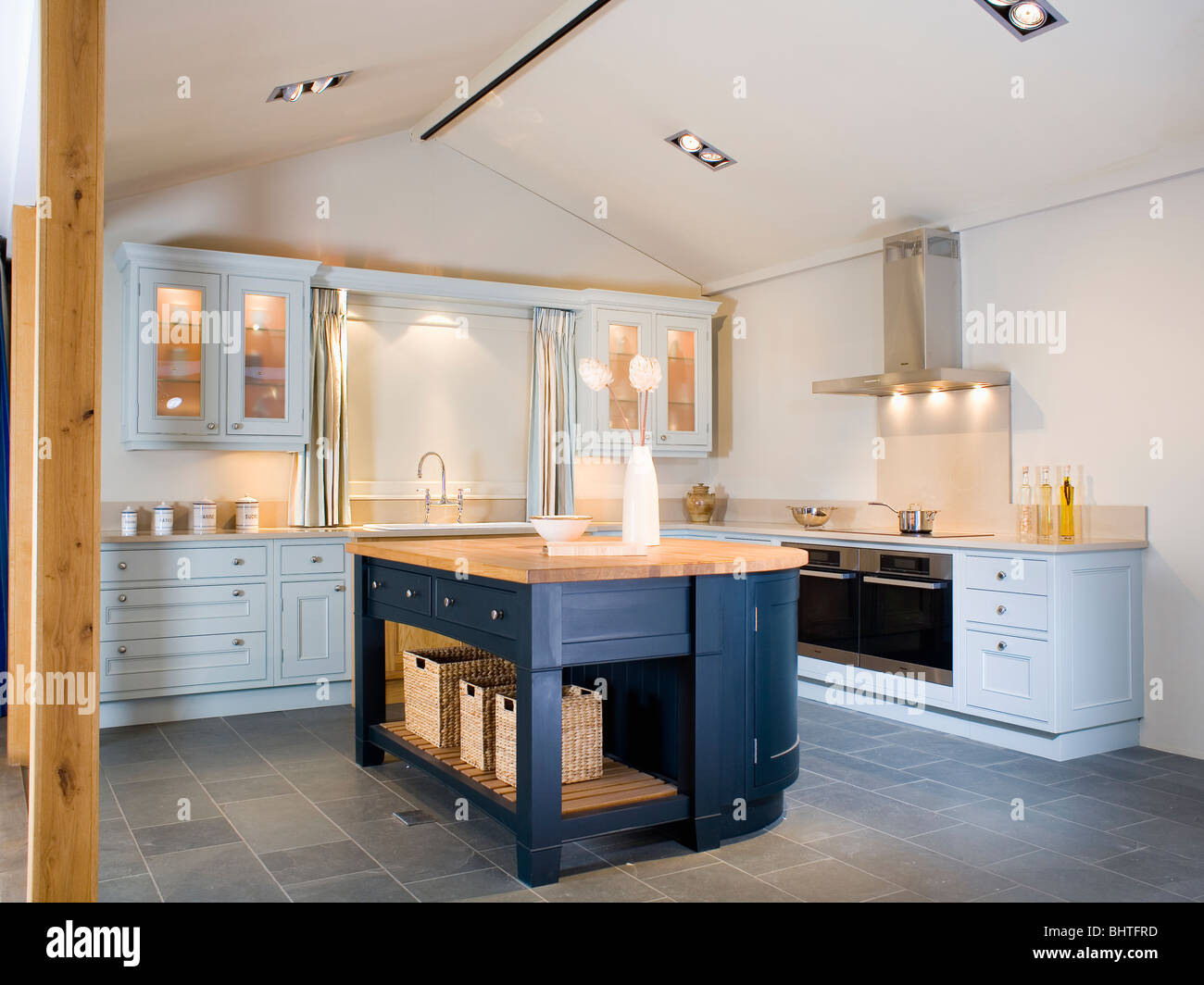 Dark blue island unit and slate flooring in modern kitchen for Dark blue kitchen units