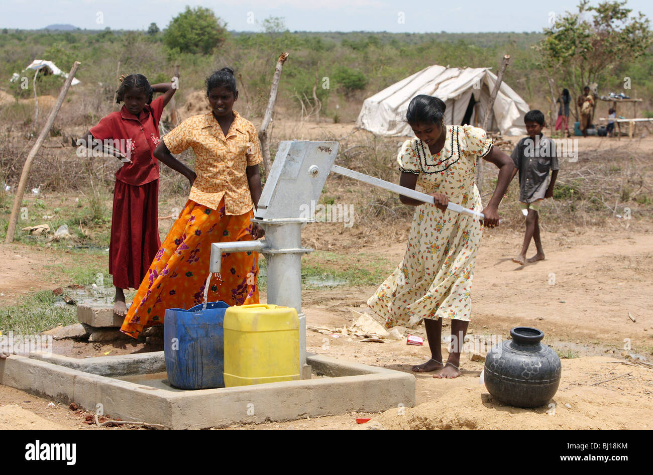 Women doing laundry at a water pump in a shelter for Internally Displaced People, Vakaneri, Sri Lanka Stock Photo