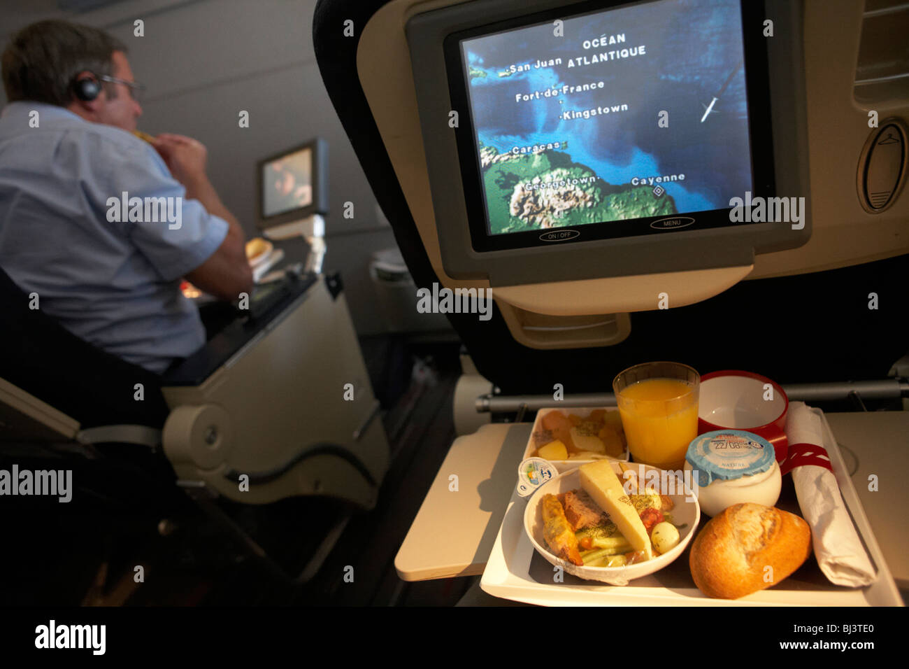 a-man-tucks-in-to-his-in-flight-meal-on-