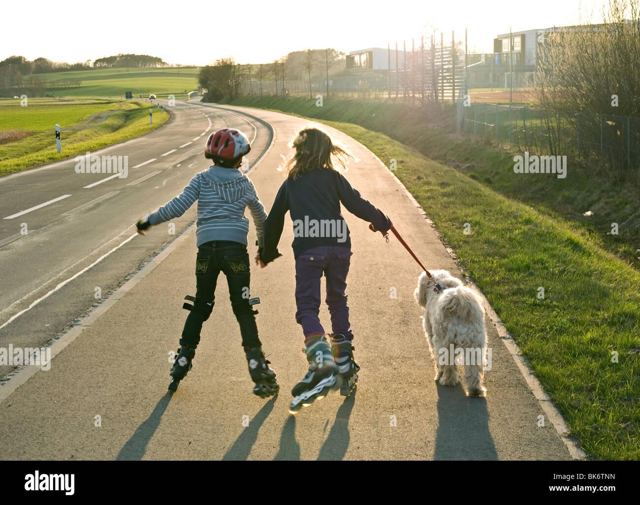 2-children-on-roller-blades-walking-pet-