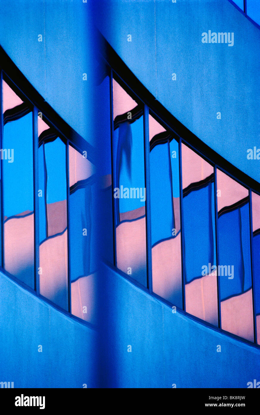 Abstract view of a modern corporate office building including reflections in the windows of the sunset sky Stock Photo