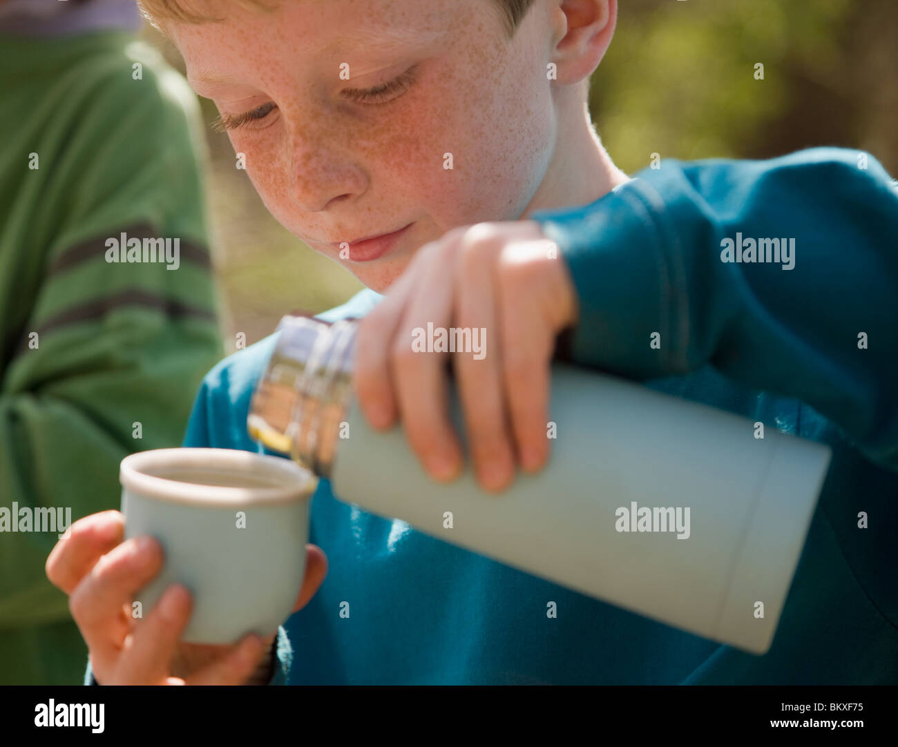 Close up of young boy pouring water from insulated flask Stock Foto