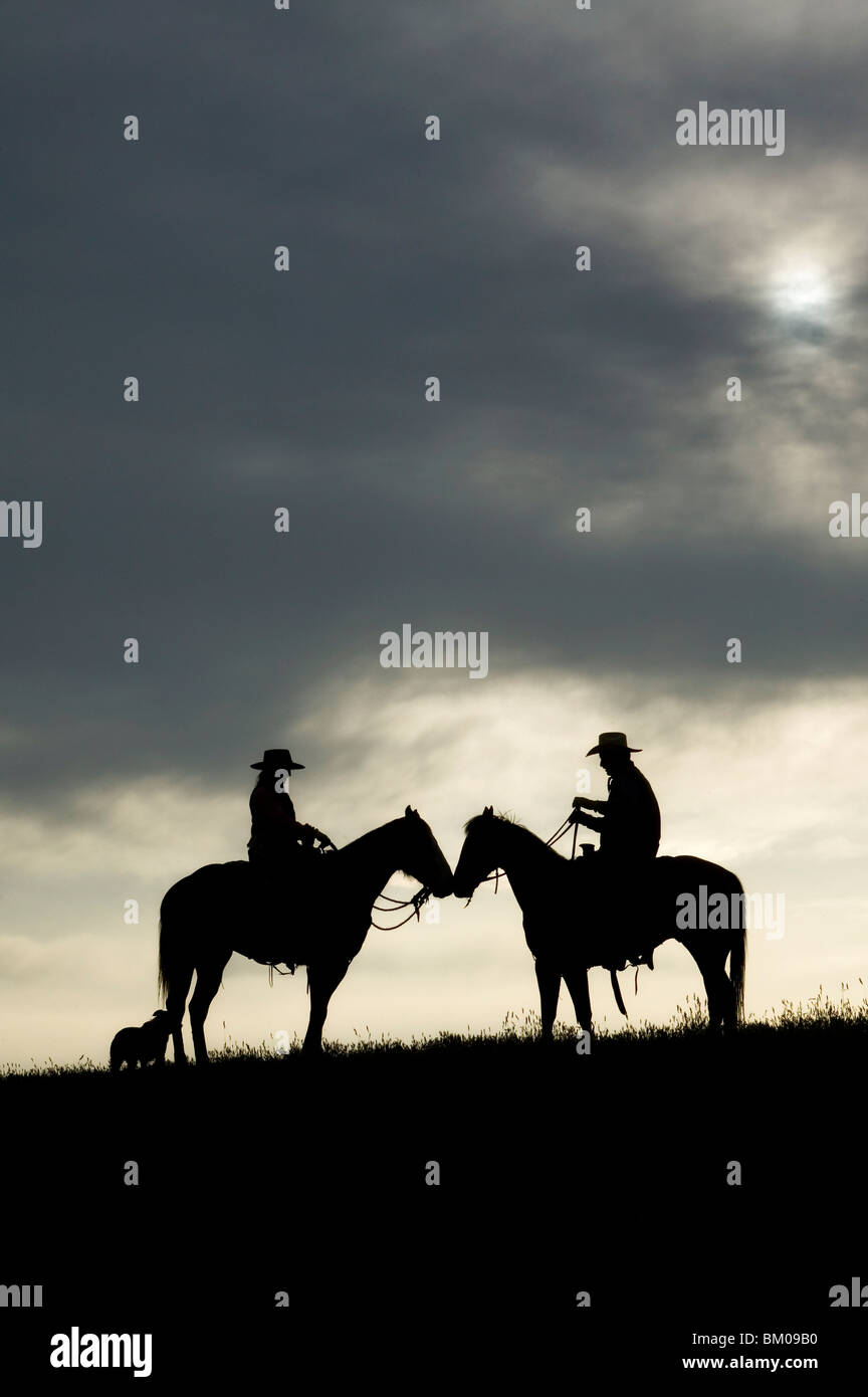 Cowboy and cowgirl on their horses at sunset Stock Photo
