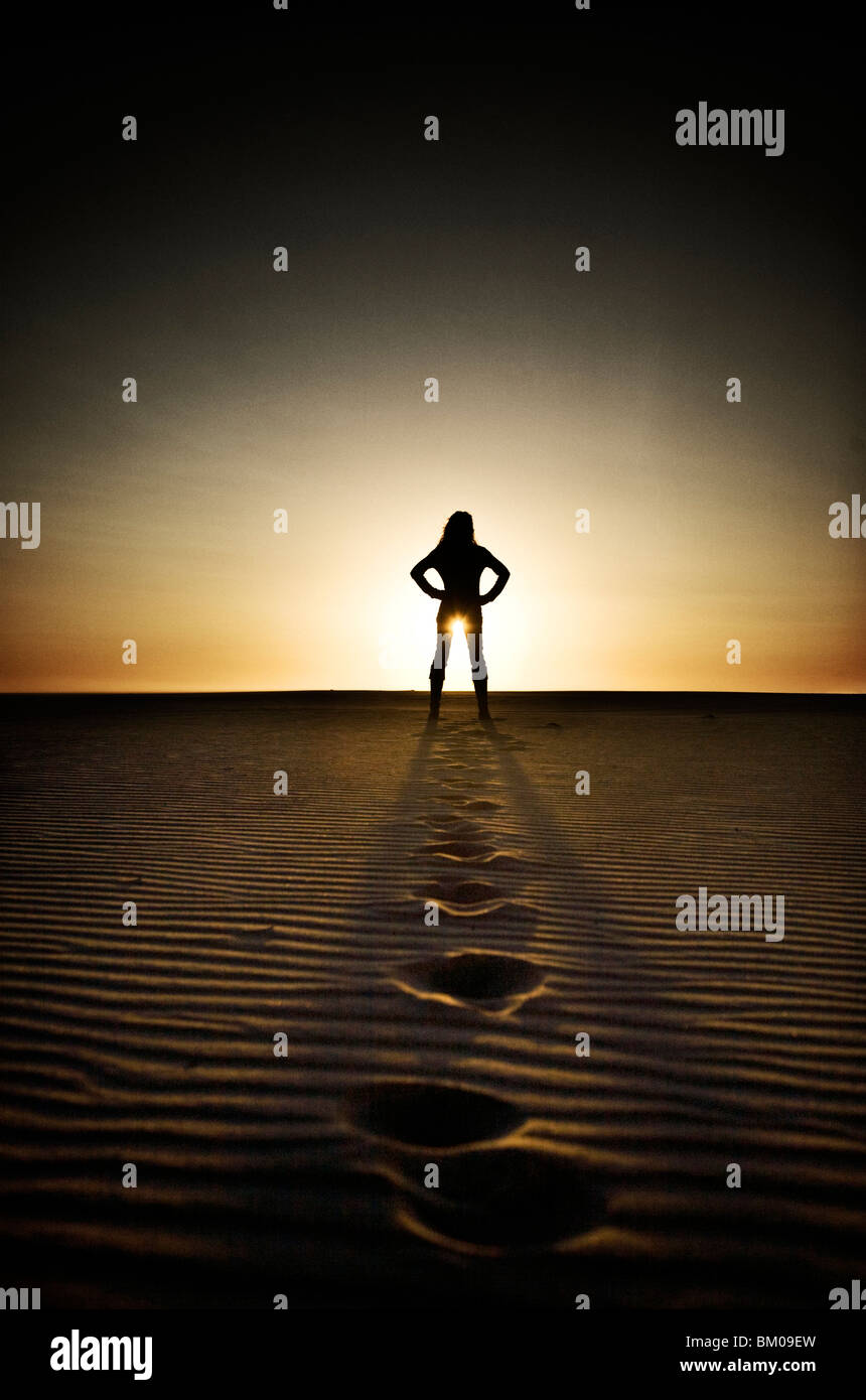 Young woman in distance standing on beach at sunset with foot prints in sand Stock Photo