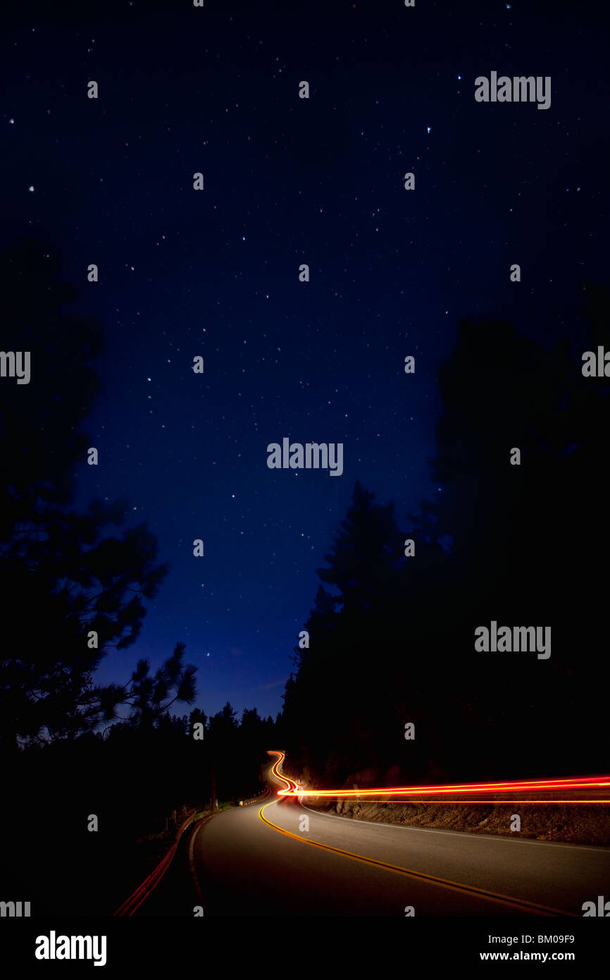 Car trails at night along a windy road in the mountains Stock Photo