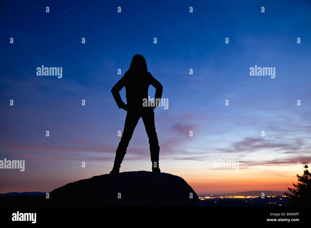 Silhouette of a woman standing on a rock at night overlooking the city lights Stock Photo