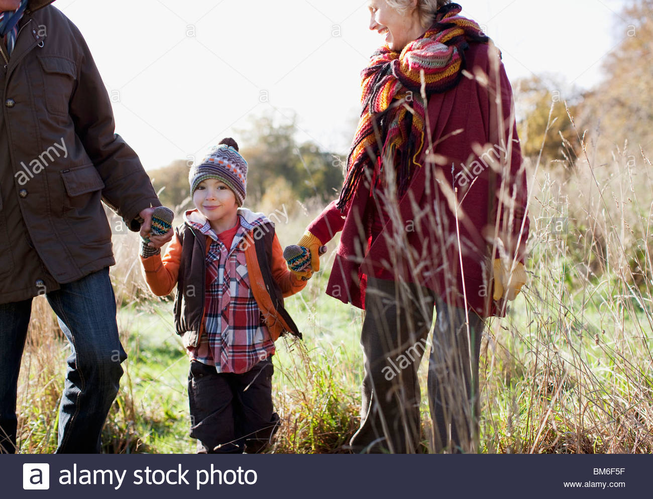 Grandparents holding hands with grandson outdoors Stock Foto