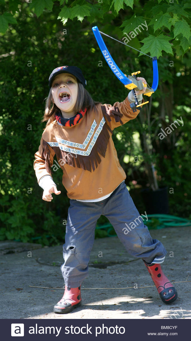 Full length little boy dressed as a Red Indian carrying his bow and arrows Stock Photo