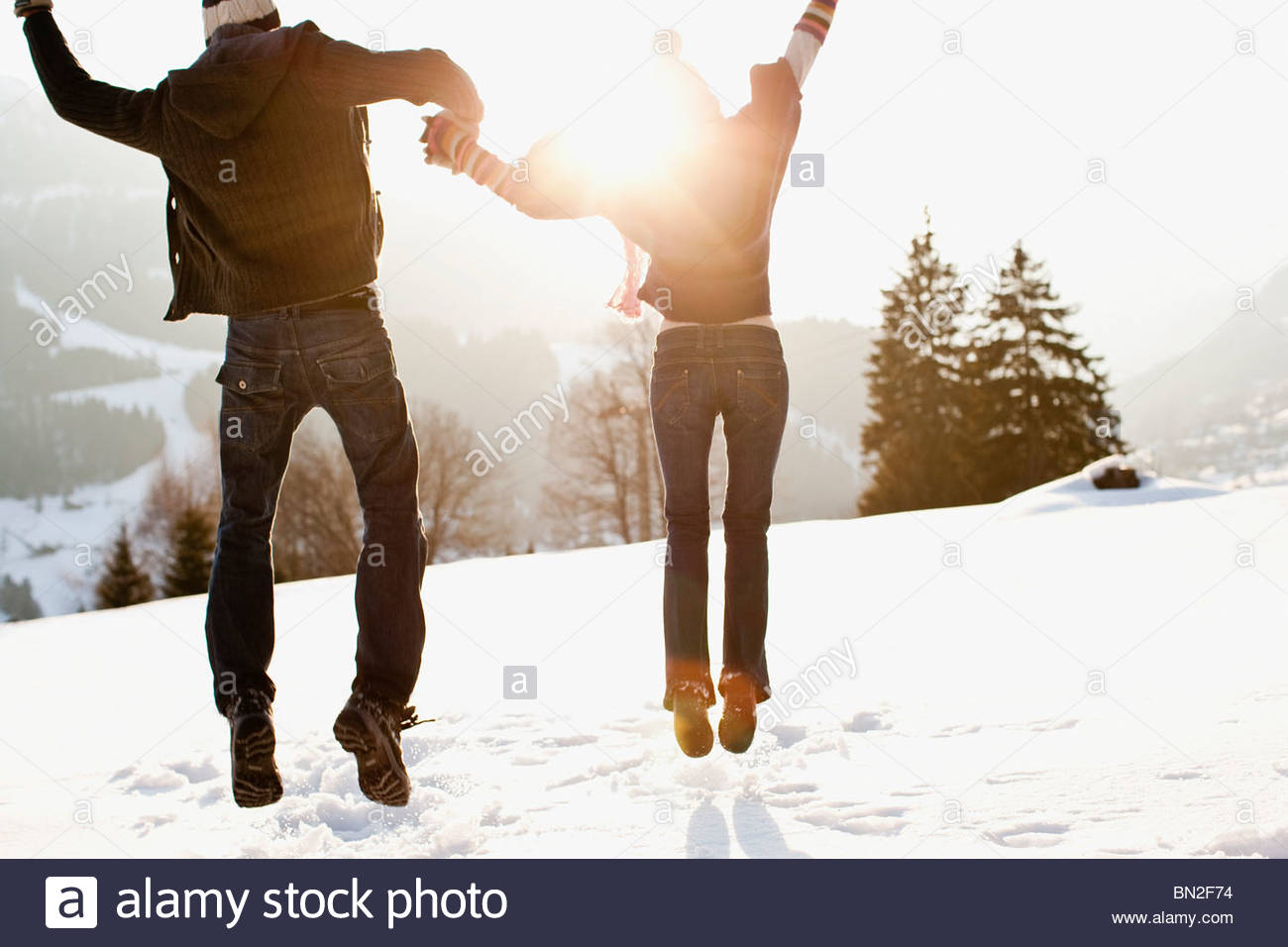 Couple jumping outdoors in snow Stock Foto