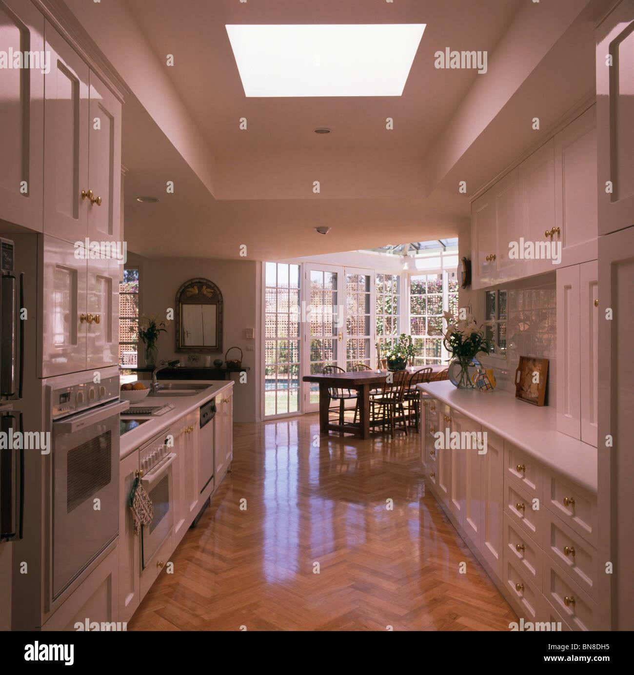 Wooden Parquet Flooring In Large Modern Galley Kitchen And