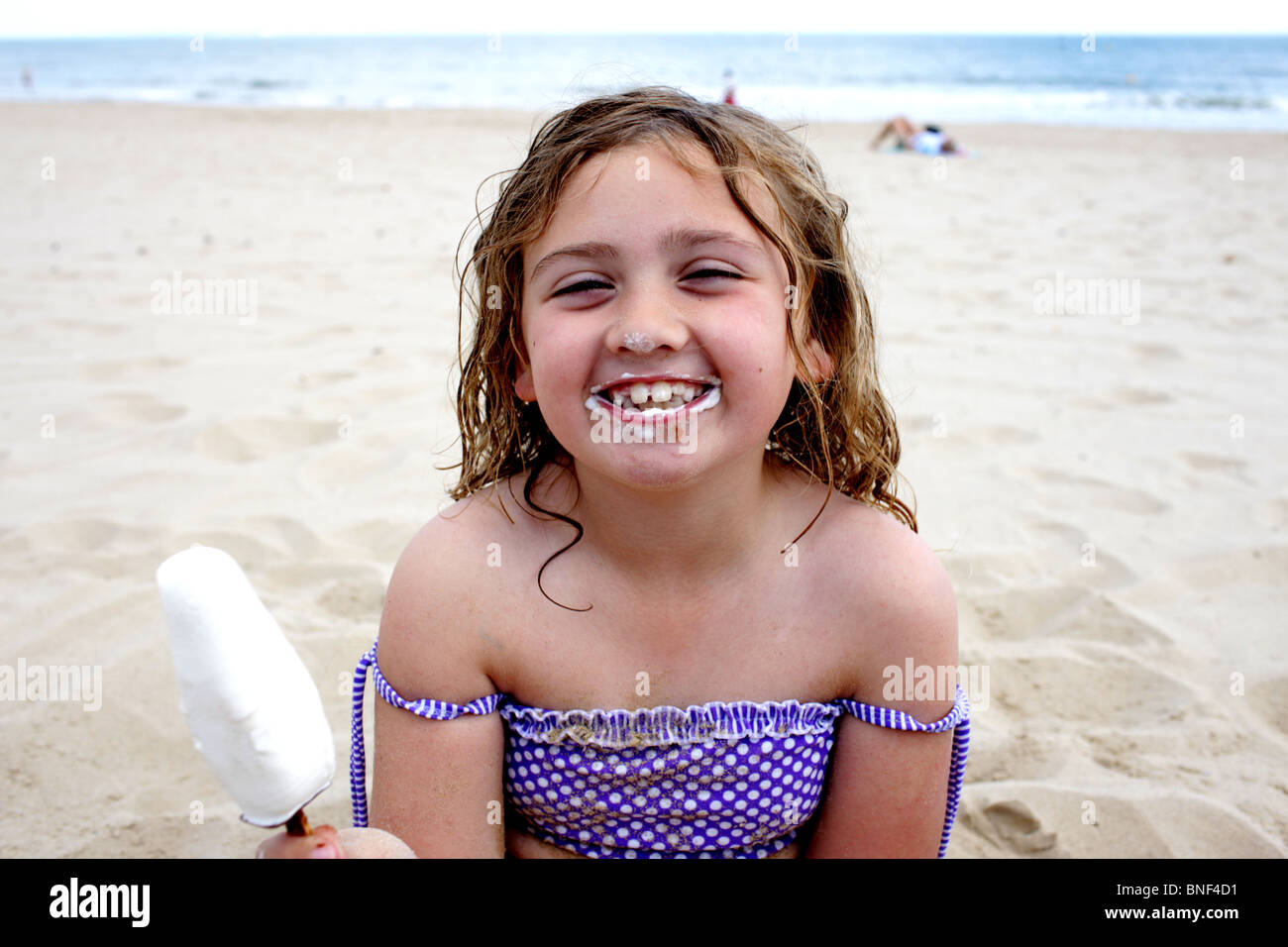 lolly model Stock Photo - Young Girl Eating Ice Lolly on Beach. Model Released