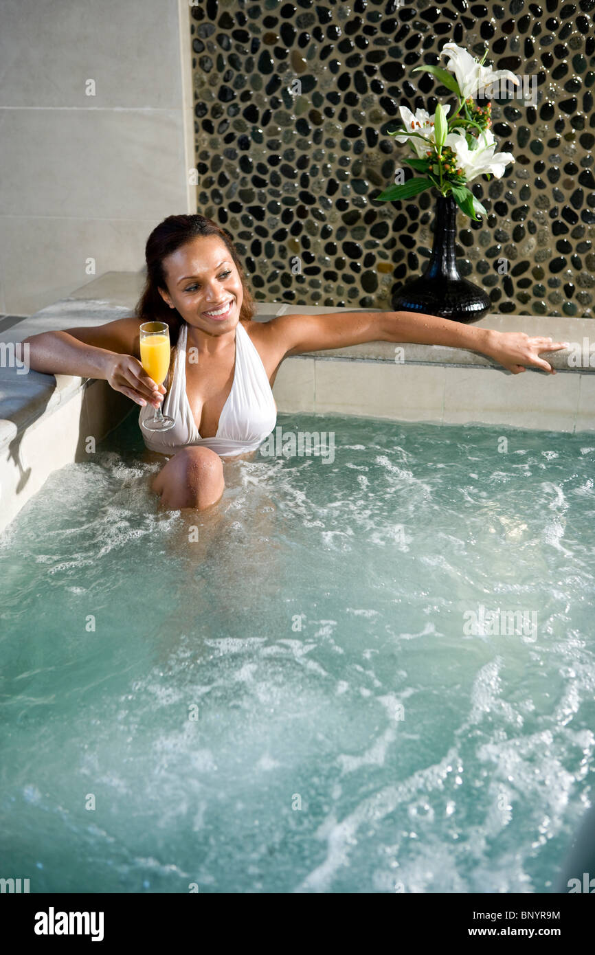young african american woman relaxing with drink in hot tub stock photo royalty free image. Black Bedroom Furniture Sets. Home Design Ideas