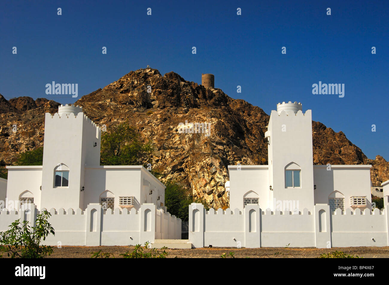 New family homes beneath an old fortress in the periphery of Muscat, Sultanate of Oman Stock Photo