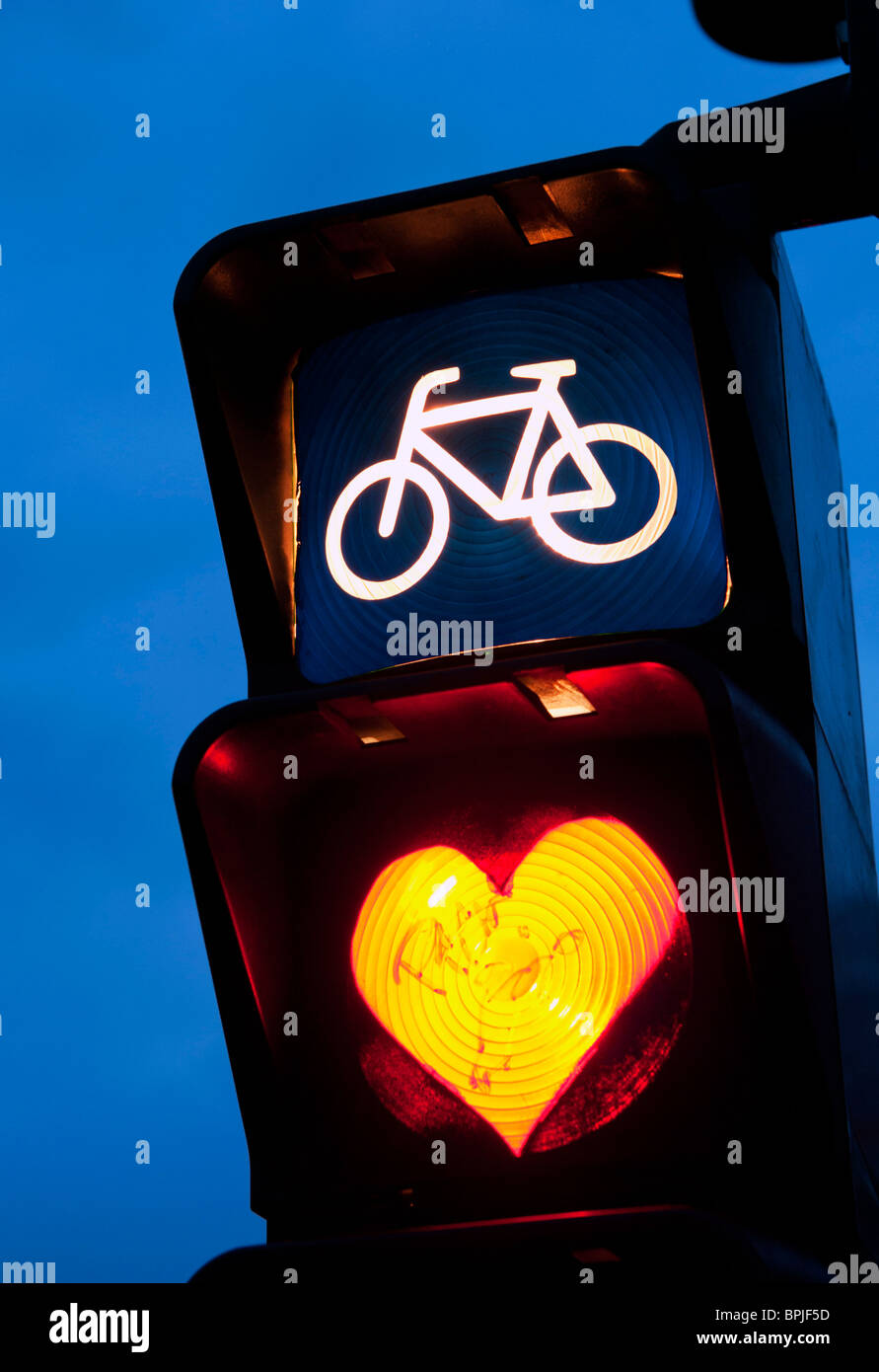 Detail of red cycle traffic stop light painted with love heart in Berlin Germany Stock Foto