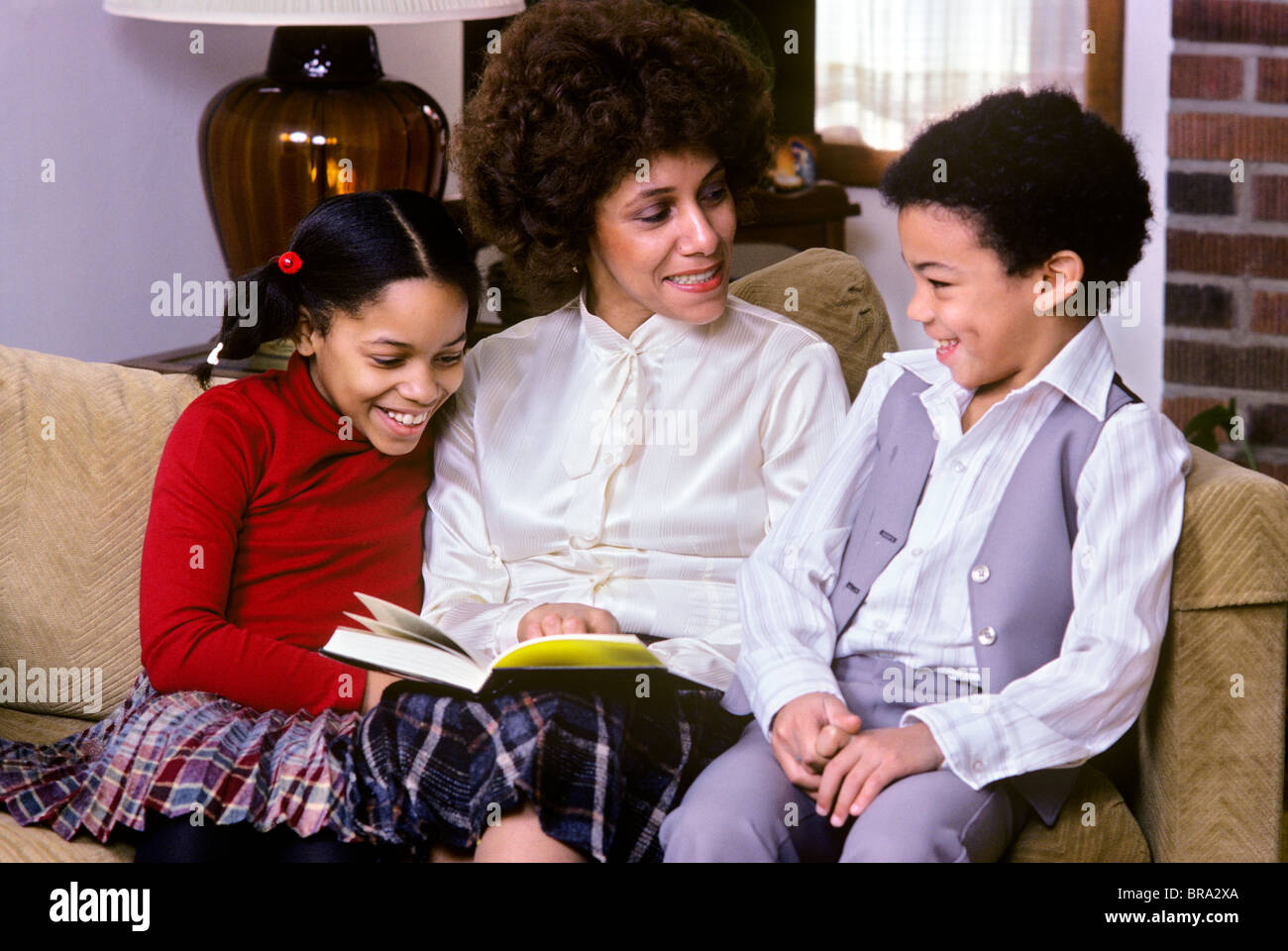 1970 1970s 1980 1980s retro african american mother sitting on couch stock photo royalty free - Sofa hars gevlochten buitenkant ...