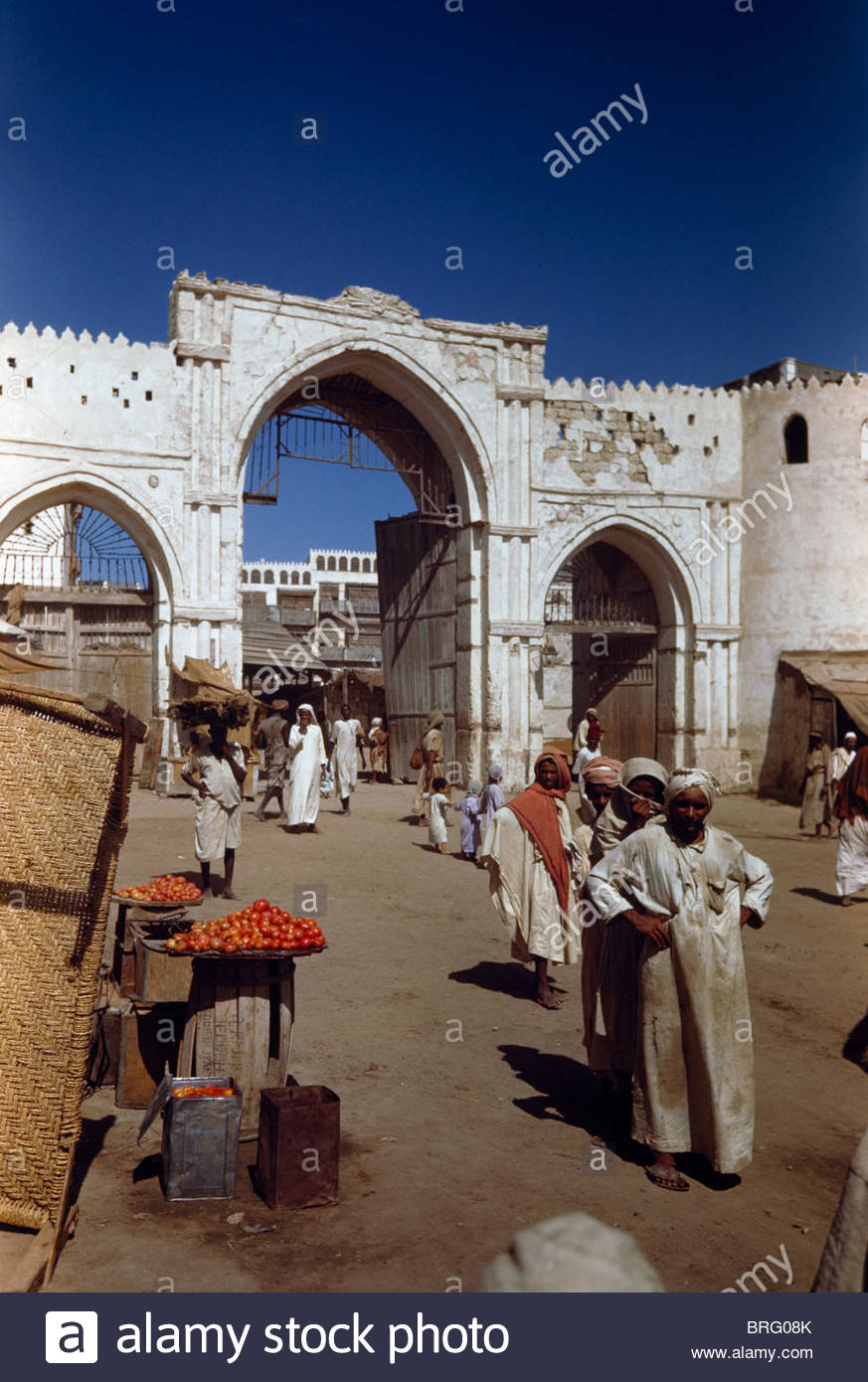 Men stand near a tomato vendor's display outside a city gate. Stock Photo