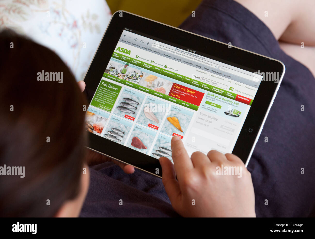 woman shopping at home online over wifi at asda shop on an ipad stock photo royalty free image. Black Bedroom Furniture Sets. Home Design Ideas