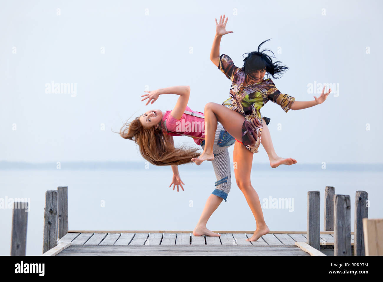 two girl  are dancing on background of water and sky Stock Foto