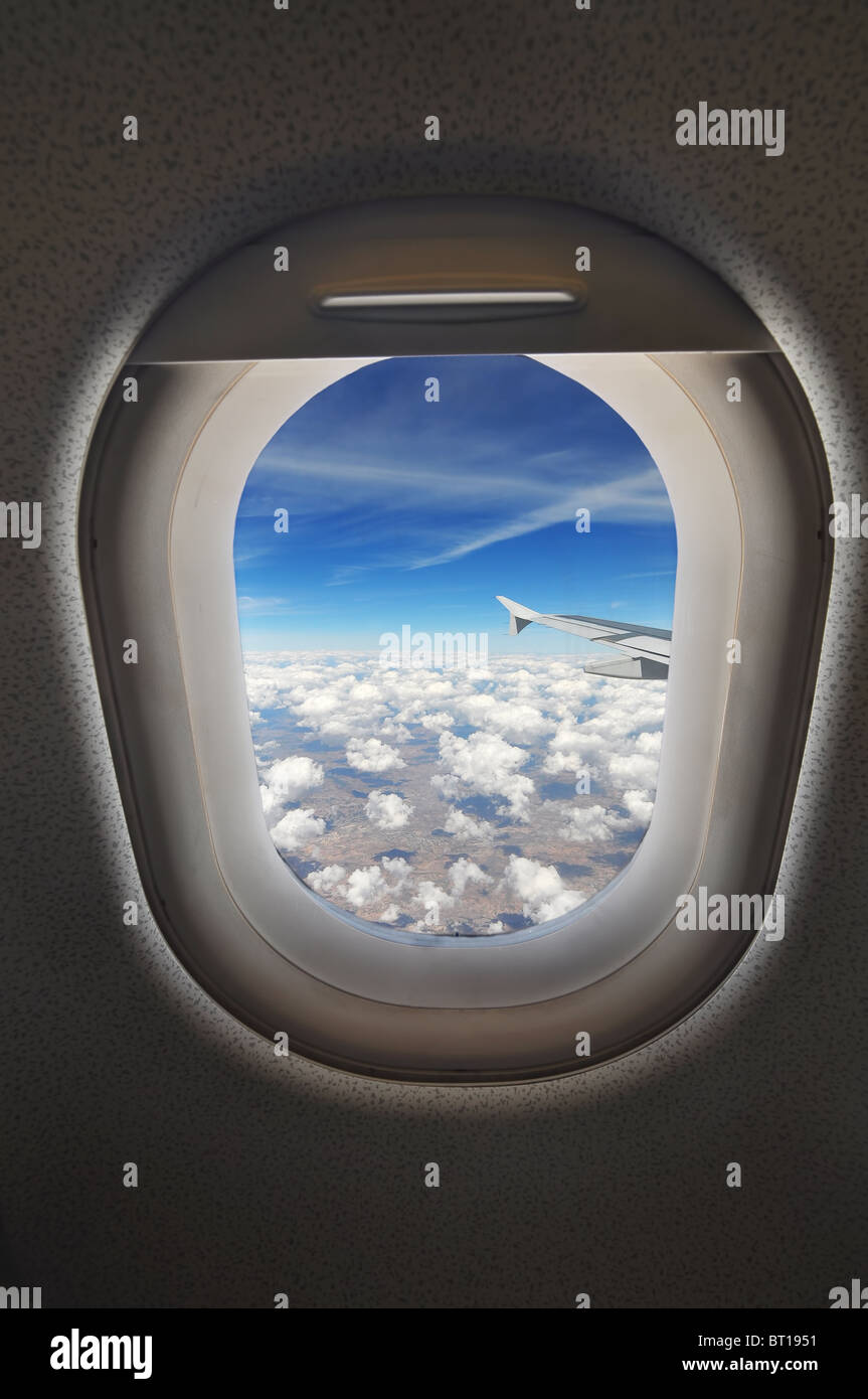 cloudscape seen through an airplane window from the passenger seat Stock Photo